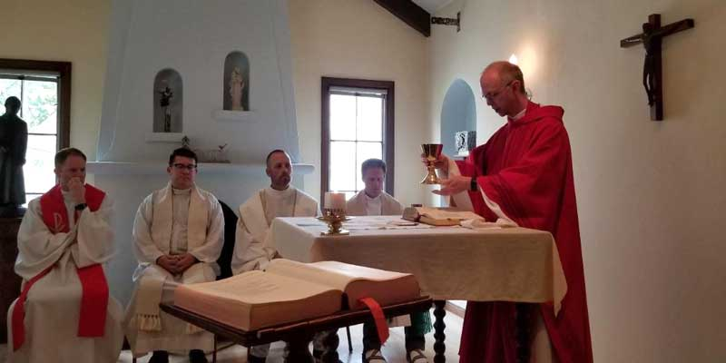 Photo: Adam Booth (right) performs the Eucharist at a symposium in Berkeley, California, in August 2018.