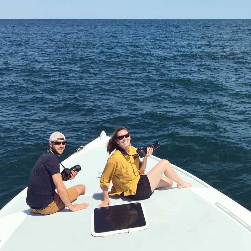 Photo: Ph.D. students Jillian Wisse and Joe Fader conducting fieldwork this summer. Cameras are a field essential, as individual whales can be identified by unique markings on their bodies and dorsal fins.